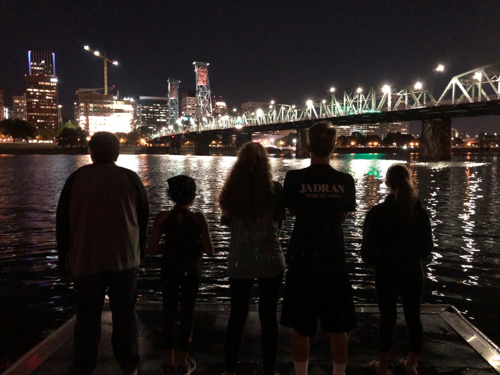 Students on field trip admiring river view at night